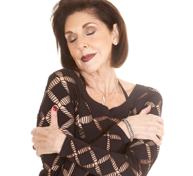 older woman black clothes arms crossed eyes closed