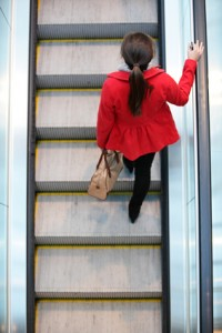 Urban people - woman commuter walking on escalator